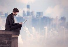 Персона продаж сидя na górze высокого здания Стоковое Изображение