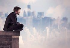 Персона продаж сидя na górze высокого здания Стоковое Изображение RF