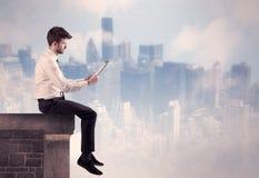 Персона продаж сидя na górze высокого здания Стоковая Фотография