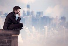 Персона продаж сидя na górze высокого здания Стоковые Изображения