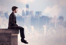 Персона продаж сидя na górze высокого здания Стоковая Фотография RF