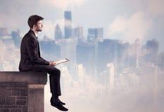 Персона продаж сидя na górze высокого здания Стоковые Изображения RF