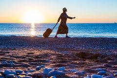 Персона путешествуя женщина идя на пляж океана на восходе солнца Стоковое Изображение
