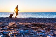 Персона путешествуя женщина идя на пляж океана на восходе солнца Стоковые Фотографии RF