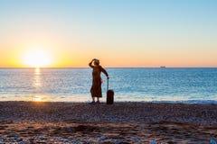 Персона путешествуя женщина оставаясь на пляже океана на восходе солнца Стоковое Изображение