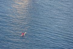 Персона работая каное/каяком, в чудесном море стоковые фото