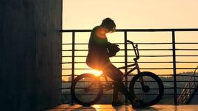 Персона сидит на велосипеде на предпосылке захода солнца, конце вверх видеоматериал