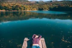 Персона сидя на пэре озером стоковые фотографии rf