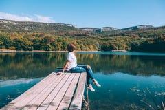 Персона сидя на пэре озером стоковые изображения rf