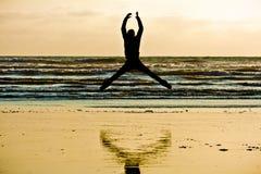 Персона скача берегом моря Стоковые Изображения