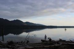 Персона стоя на краю озера на заходе солнца стоковые изображения rf