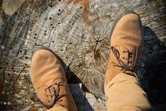 Персона с брюками и ботинками в естественных теплых цветах, стойках на деревянном хоботе, личной точке зрения стоковое изображение