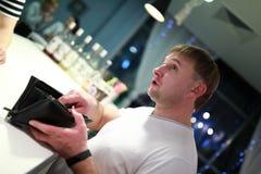Персона с портмонем на баре стоковая фотография