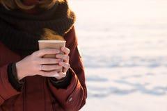 Персона с чашкой горячего кофе outdoors на заходе солнца Стоковые Фото
