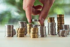 Персона штабелируя монетки на таблице, концепции вклада Стоковое Фото