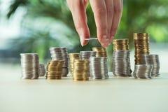 Персона штабелируя монетки на таблице, концепции вклада Стоковые Изображения