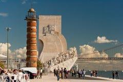 Перспектива берега реки в Лиссабоне Прогулка людей, сидит на террасе Рыболовы, памятник для исследователей и 25 de Abril Мост Стоковые Фото
