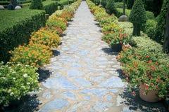 Перспектива красивых идя путей в пользе сада цветков как b Стоковые Фотографии RF