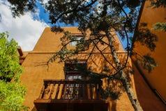 Перспектива смотря вверх на высокорослом soutwestern здании самана штукатурки с балконом с консолями на крыше и деревьях обрамляя стоковые фото