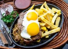 Перуанская латино-американская еда Lomo pobre lo Жалуйтесь зажаренные whit фрай и яичка француза картошек Стоковые Фото