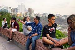 Перуанские люди и туристы наблюдая заход солнца и принимая selfies стоковые фотографии rf