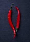 2 перца горячих chili на черной предпосылке Стоковая Фотография