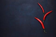 3 перца красных chili на синей каменной предпосылке Стоковые Изображения