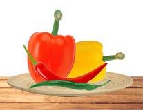 Перцы желтого и красного перца паприки и горячих чилей на плите Стоковое Фото