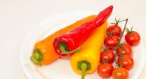 Перцы и томаты на белой плите Стоковое Изображение RF
