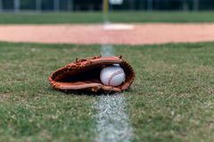 Перчатка и шарик бейсбола на протухшей линии стоковое фото