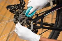 Перчатка руки крупного плана нося белая держа затирание губки на цепи велосипеда металла, механически концепции ремонта Стоковые Фото