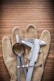 Перчатки безопасности кожи рассекателя верньерного масштаба на деревянной доске Стоковые Изображения RF