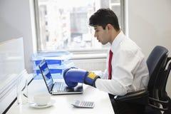 Перчатки бокса молодого индийского бизнесмена нося пока использующ компьтер-книжку на столе офиса Стоковые Изображения RF
