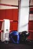 Перчатки бокса, headgear, бутылка с водой и полотенце в боксерском ринге Стоковая Фотография