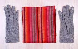 Перчатки и шарф на деревянной предпосылке, одежда на осень или зима Стоковые Изображения RF