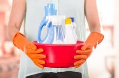 Перчатки крупного плана оранжевые держа красное ведро чистящих средств и усмехаясь к камере, housecleaning концепции стоковые изображения