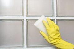 Перчатки носки женщины резиновые очищая стену плитки Стоковые Фотографии RF
