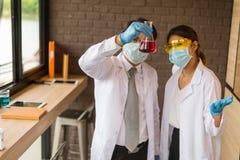 Перчатки носки человека и женщины ученого голубые держа стеклянную пробирку Химик рассматривает химическую пробирку, науку, докто Стоковая Фотография RF