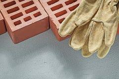 Перчатки оранжевых кирпичей кожаные работая на buildin конкретной поверхности Стоковая Фотография