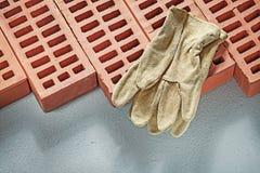 Перчатки оранжевых кирпичей кожаные работая на constru конкретной поверхности Стоковое Изображение RF