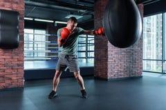 Перчатки сильного спортсмена кладя в коробку трудно- нося красные стоковая фотография rf