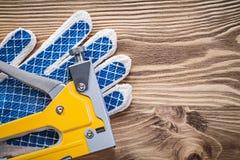 Перчатки штапеля конструкции защитные работая на деревянной доске суровой Стоковое Фото