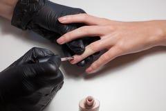 Перчатки Manicurist черные делая маникюр на салоне красоты на белой предпосылке Маникюр красит обнажённую фигуру красивейше Стоковые Изображения