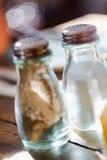 Перчинки старой моды стеклянные и шейкер соли на деревенском деревянном t Стоковое Фото