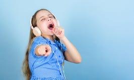 Песня для каждой эмоции Прелестная любительская певица песни караоке на голубой предпосылке Милый небольшой делать ребенка вокаль стоковое фото rf