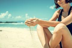Песок как время смещает через ваши пальцы Девушка держа предпосылку моря песка Концепция каникул в более теплых странах Стоковая Фотография RF