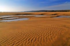 Песок красиво patterened и вода расколотый влажный отражая голубое небо Стоковые Фото