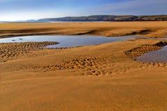 Песок красиво patterened и вода расколотый влажный отражая голубое небо Стоковое Фото