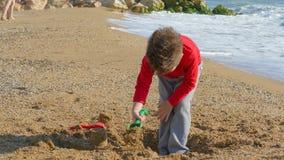 Песок мальчика выкапывая на пляже сток-видео