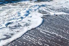 Песок моря помыл волнами на восходе солнца Стоковые Изображения
